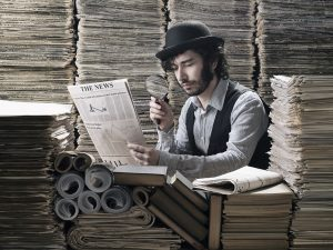 Young man in old fashioned costume making research among newspapers, looking through magnifying glass