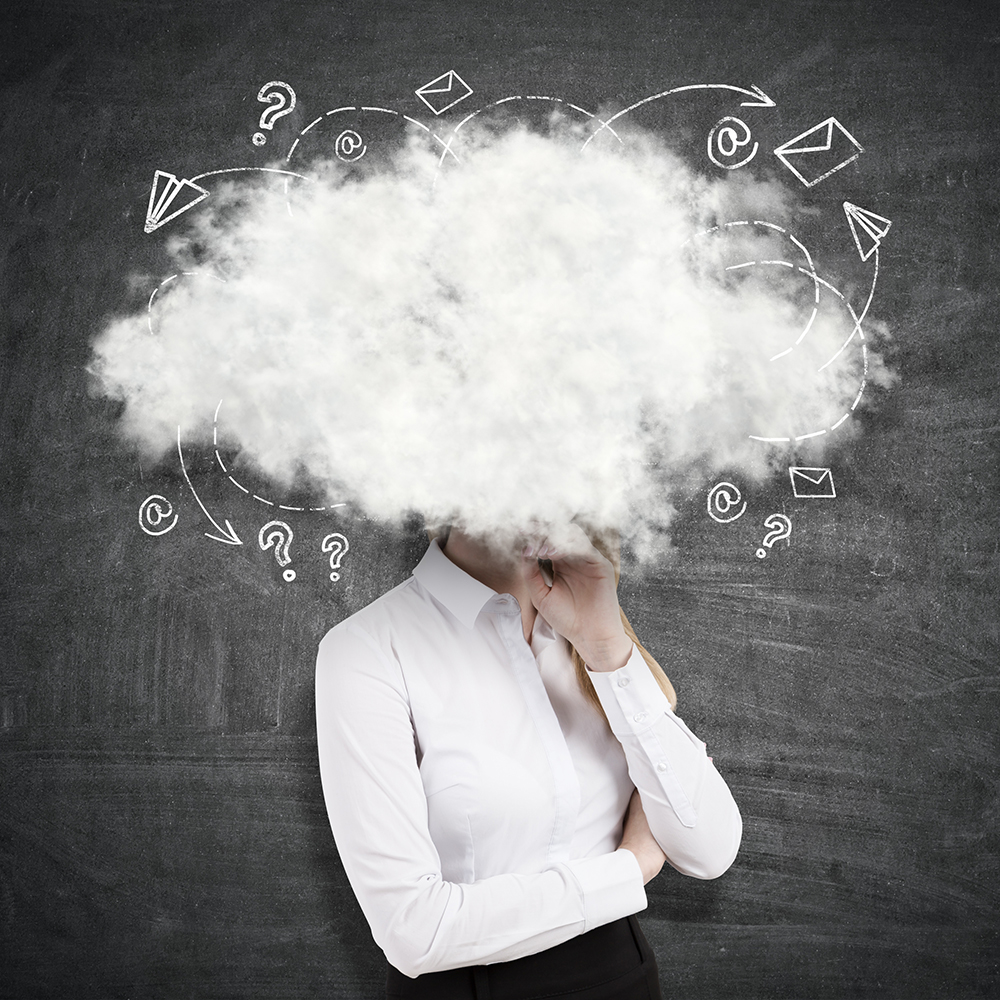 Side view of young businesswoman with head in the clouds on chalkboard background. Writer's block concept