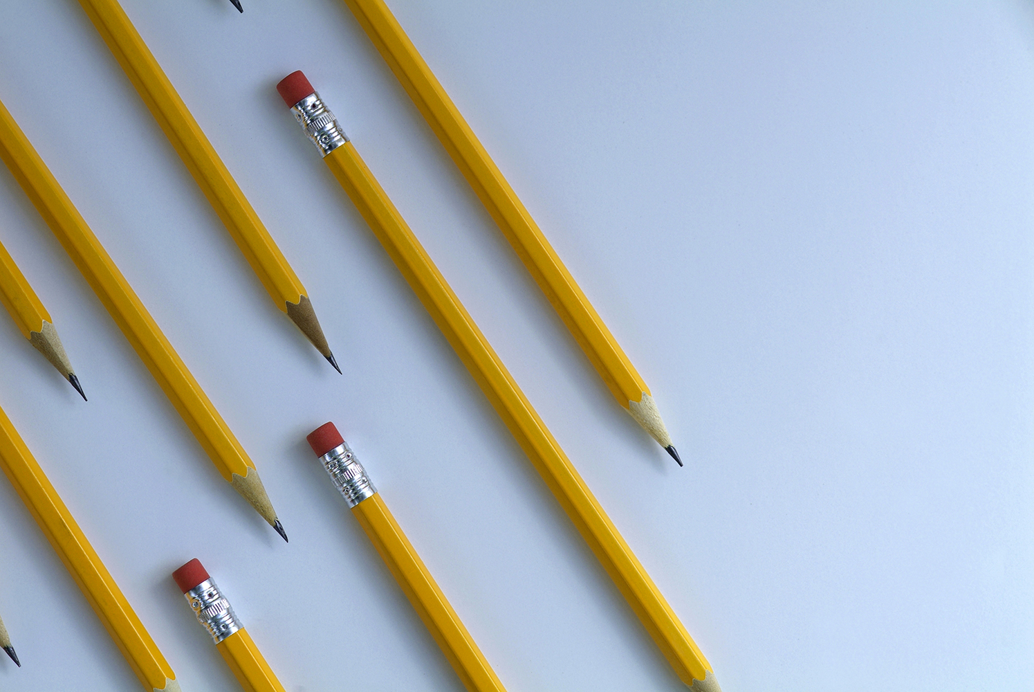 Several yellow pencils on diagonal and parallel to each other on white