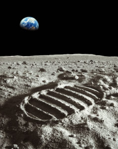 Footprint of astronaut on the moon with earth above the horizon.